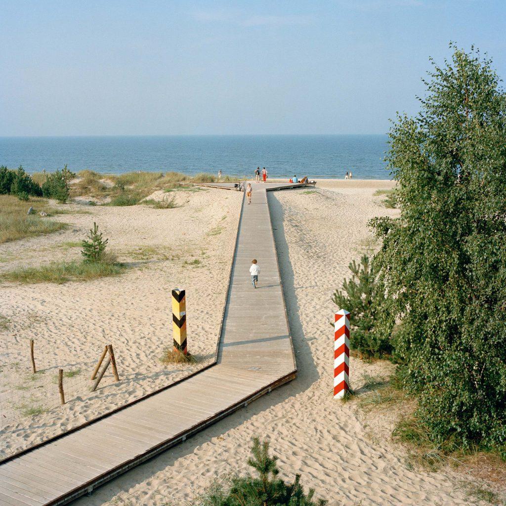 Chemin en planches sur une plage marquant la frontière