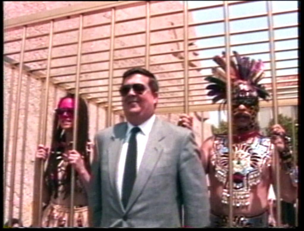 Photogramme du film montrant un homme blanc en costume-cravate devant une cage qui retient deux homme blancs costumés.