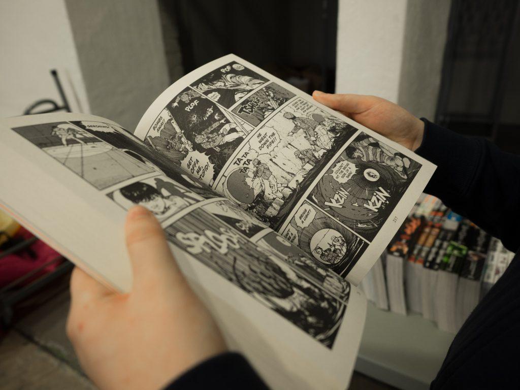 Un lecteur feuillette une bande dessinée