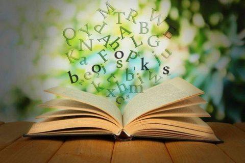 Image numérique d'un livre ouvert surmonté d'un nuage de lettres
