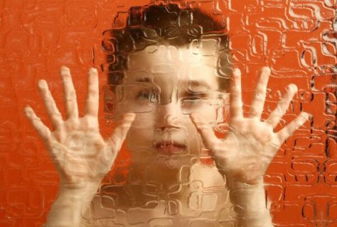 Photo d'un enfant derrière une vitre opaque