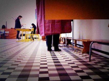 Photographie d'un homme dans un isoloir lors des élections régionales 2014
