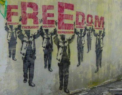 Pochoir avec 7 personnages tenant chacun une lettre du mot Freedom pour défendre la liberté de parole, de pensée, de religion, d'expression, d'assemblée, de choix et d'association