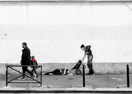 Passants devant une oeuvre de street art montrant un homme à terre