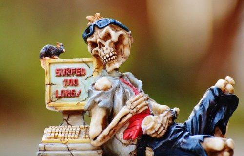 Figurine humoristique représentant un squelette appuyé sur un écran d'ordinateur