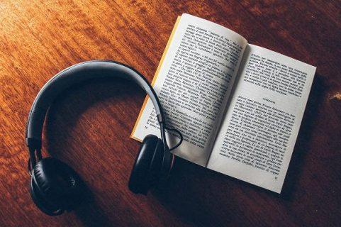Photo d'un livre ouvert à côté d'un casque de musique