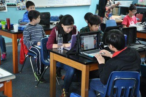Photographie d'élèves dans une salle de classe avec des ordinateurs