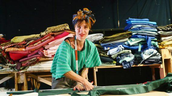 femme posant devant des textiles