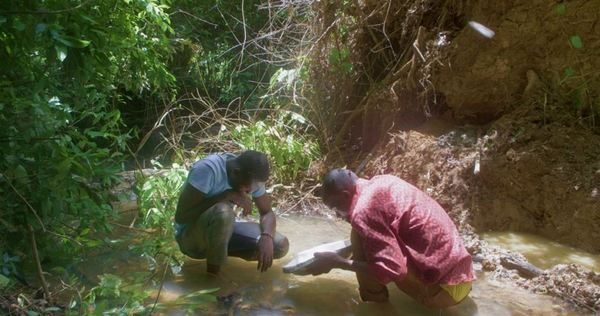 Deux hommes accroupis dans une rivière