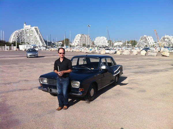 Mathieu Sapin appuyé contre une voiture