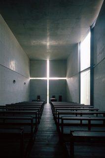 L'intérieur d'une église sombre partiellement éclairée par la lumière qui entre à travers une croix au mur au fond et la porte d'entrée à droite