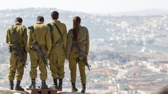 3 soldats masculins et un soldat féminin de dos regardent un beau paysage d'une ville en Israël