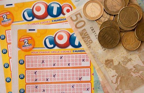 Une grille de loto, un billet de 50€ et des pièces de monnaie.