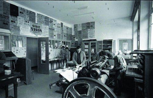 Vue de l'intérieur de l'imprimerie, plusieurs patients en train d'y travailler