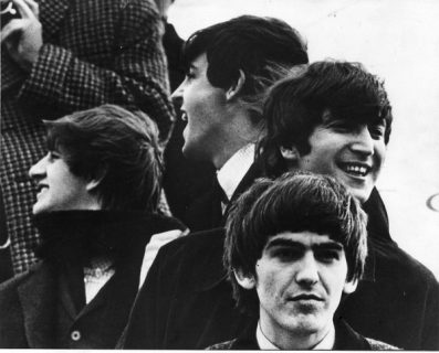 Les Beatles, dehors, souriants dans quatre directions