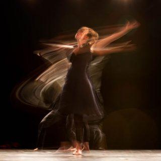 Une femme en tenue noire danse sur scène, elle est floue.
