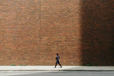 Une femme marche devant un immense mur en brique