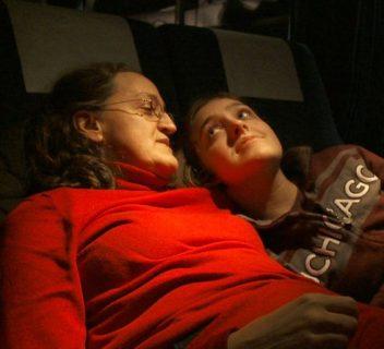 Deux femmes se regardent, allongées et souriantes dans un train