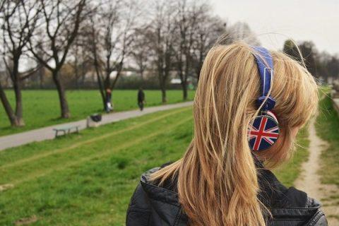 Une femme de dos dans la campagne, un casque audio sur les oreilles