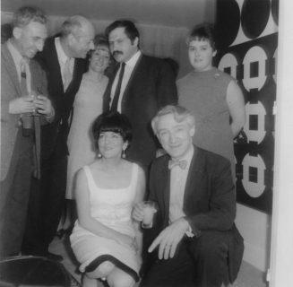 Denise René accroupie au milieu d'artistes dans sa galerie
