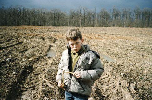 Un garçon fronce les sourcils dans un champ boueux
