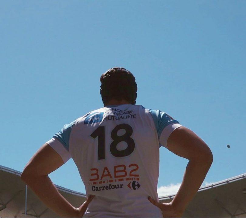 Un joueur de rugby de dos regarde le ballon qui arrive haut dans le ciel