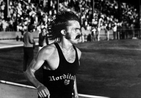 Steve Prefontaine en plein effort : cheveux longs et moustache, les sourcils froncés, il termine une course sur une piste d'athlétisme.