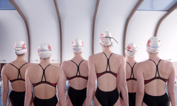 Des nageuses de dos devant une piscine