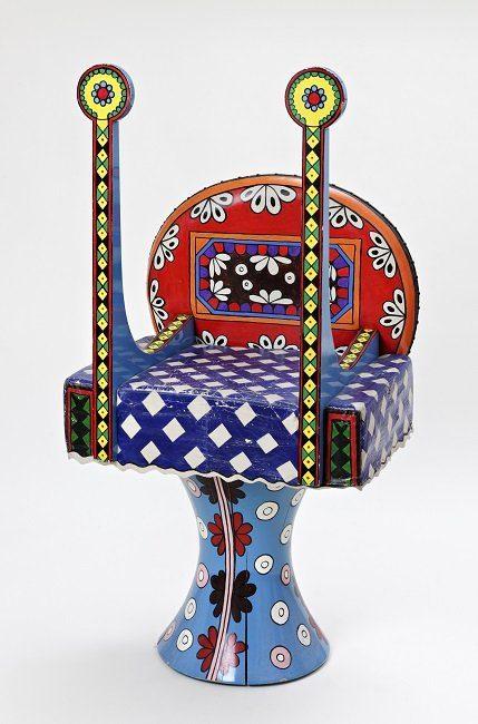 Fauteuil avec un pied cylindrique bleu ciel et avec des motifs ronds, assise bleu cobalt avec motifs géométriques, deux bras montants aux motifs géométriques dans les tons jaunes, dossier rouge et orange avec des motifs.