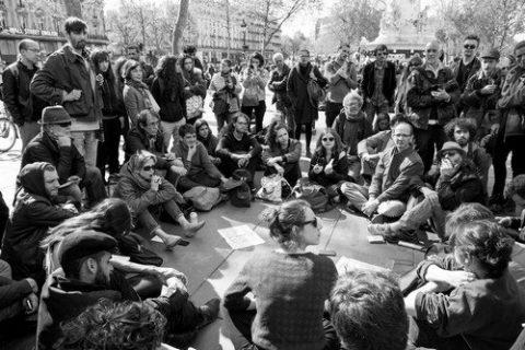 Nuit debout : groupe de personnes assises par terre en cercle place de la République