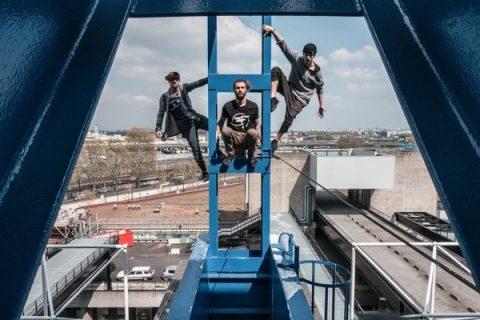 Trois membres du groupe French Freerun Family posant sur une structure structure métallique dominant une ville