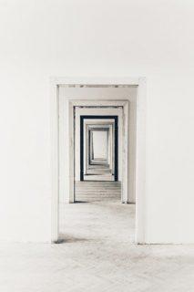 Des portes ouvertes en enfilade, se suivent dans un long couloir - ou peut-être s'agit-il d'un enchainement de pièces vides. Le sol et les murs sont peints en blanc, de même que l'encadrement des portes - sauf une porte bordée de noir.