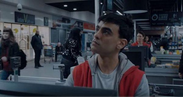 Extrait de la série L'Effondrement. Un jeune caissier regarde un écran de télévision.