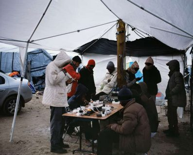 Des migrants rechargent leurs téléphones sous une tente.