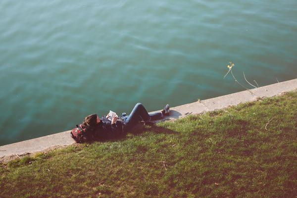 Une jeune femme lit au bord de l'eau.