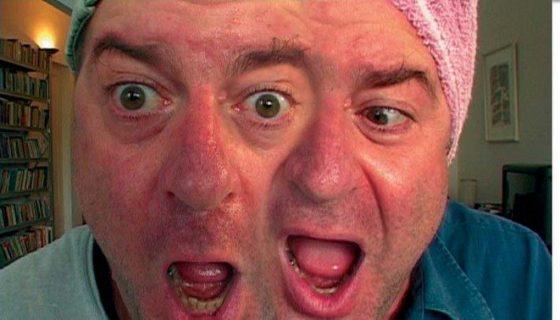 Avi Mograbi dédoublé face caméra, une serviette sur la tête