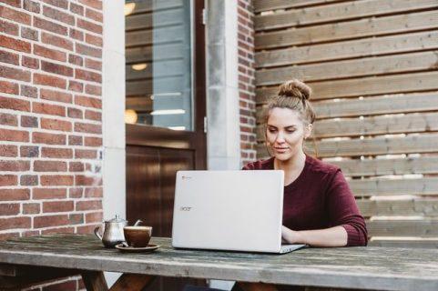 Une femme devant son ordinateur, en extérieur, sur une table de jardin