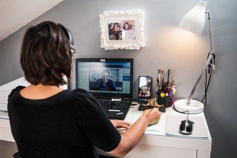 Une femme en visioconférence sur son bureau personnel