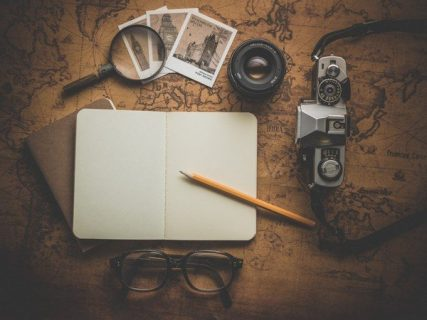 Carnet, appareil photo et lunettes disposés sur un planisphère