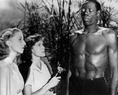 Un homme noir zombie, les yeux blancs, et deux femmes blanches étonnées à ses côtés.