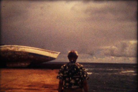 Un homme de dos face à un canot et à l'océan.