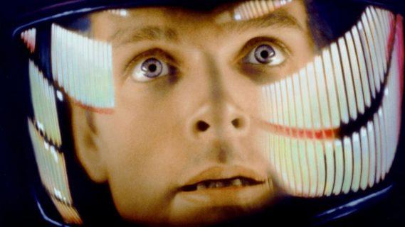 Un astronaute derrière son casque regarde, le regard surpris et effrayé.