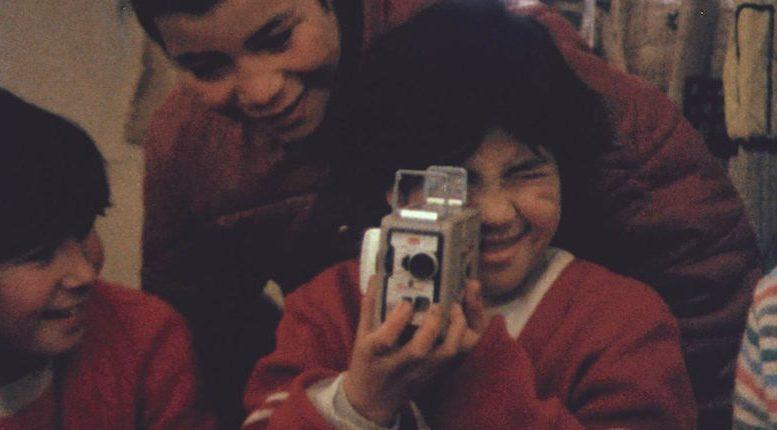 Un enfant regarde dans un caméra 8mm.