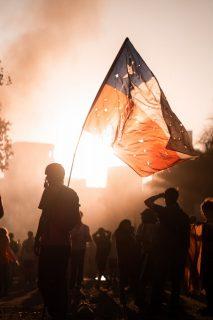 homme brandissant un drapeau dans un manifestation de nuit