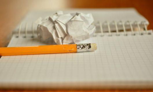 Un crayon sur un cahier, une feuille chiffonnée.