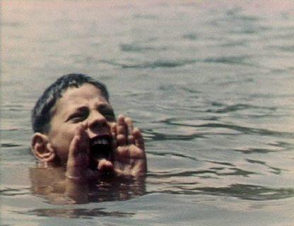 Photo d'un enfant plongé dans l'eau dont on ne voit que la tête, qui crie avec les mains en porte-voix