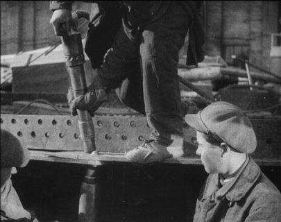 Trois hommes travaillent le métal.