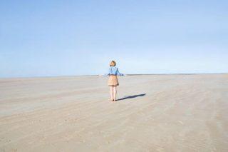 Une jeune femme de dos sur une plage